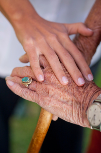 Close up of care assistants hand reassuring senior womanの写真素材 [FYI03513745]