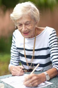 Senior woman drawing in retirement villa gardenの写真素材 [FYI03513757]