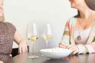 Mid adult female friends drinking at table with wine and popcornの写真素材 [FYI03513828]