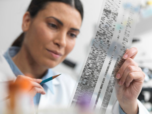 Female scientist examining DNA gel in laboratory for genetic researchの写真素材 [FYI03513942]