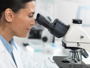Female scientist viewing sample slide for clinical test in laboratoryの写真素材 [FYI03513943]