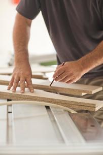 Upholsterer measuring planks of wood chipの写真素材 [FYI03514287]