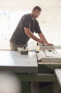 Upholsterer preparing planks on miter sawの写真素材 [FYI03514289]