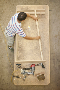Upholsterer constructing a wooden frame on tableの写真素材 [FYI03514298]