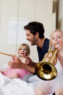 Father and two young daughters playing musicの写真素材 [FYI03514478]