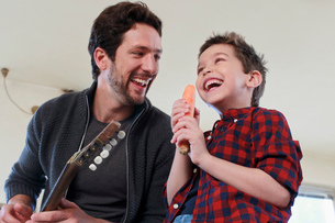 Father and son with guitar and carrot microphoneの写真素材 [FYI03514481]