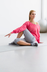 Young woman sitting on exercise matの写真素材 [FYI03514545]