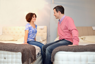 Couple sitting on beds in furniture shop showroomの写真素材 [FYI03514637]