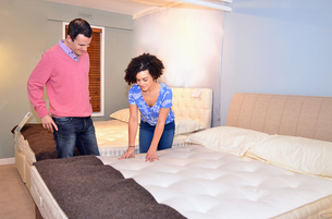 Couple testing beds in furniture shop showroomの写真素材 [FYI03514639]