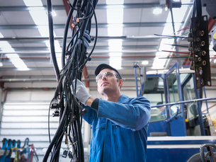 Engineer installing new electrics in truck repair factoryの写真素材 [FYI03514658]