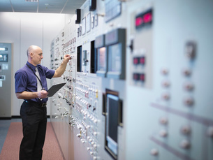 Engineer inspecting nuclear power station control room simulatorの写真素材 [FYI03514764]
