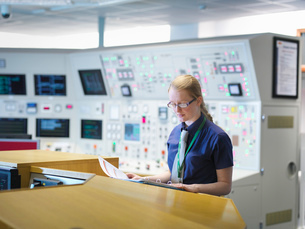 Female operator reading notes in nuclear power station control room simulatorの写真素材 [FYI03514773]