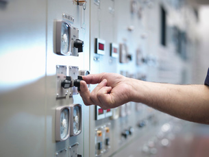 Close up of hand adjusting control in nuclear power station control room simulatorの写真素材 [FYI03514775]