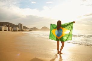 Woman holding Brazilian flag on Copacabana Beach, Rio, Brazilの写真素材 [FYI03514835]