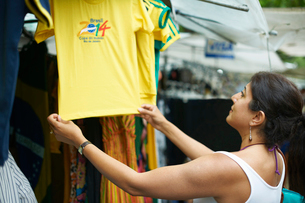 Mature woman looking at brazilian football shirt on market stall, Ipanema, Rio De Janeiro, Brazilの写真素材 [FYI03514841]