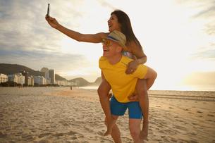 Couple taking self portrait on smartphone, Copacabana beach, Rio De Janeiro, Brazilの写真素材 [FYI03514844]