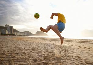 Mid adult man playing soccer on Copacabana beach, Rio De Janeiro, Brazilの写真素材 [FYI03514847]
