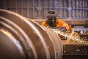 Worker grinding metal construction in marine fabrication factoryの写真素材 [FYI03515012]