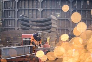 Worker grinding metal construction in marine fabrication factoryの写真素材 [FYI03515014]