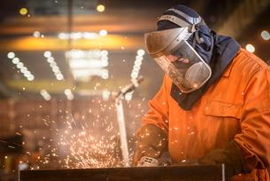 Worker grinding metal construction in marine fabrication factoryの写真素材 [FYI03515015]