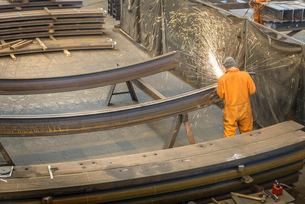 Worker grinding metal construction in marine fabrication factory, high angle viewの写真素材 [FYI03515019]