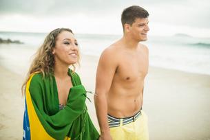 Young couple strolling on beach, woman wrapped in brazilian flag, Ipanema Beach, Rio de Janeiro, Braの写真素材 [FYI03515269]
