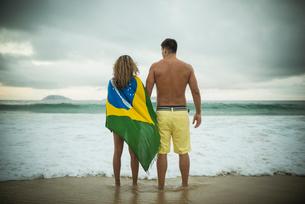 Young couple, woman wrapped in brazilian flag, Ipanema Beach, Rio de Janeiro, Brazilの写真素材 [FYI03515270]