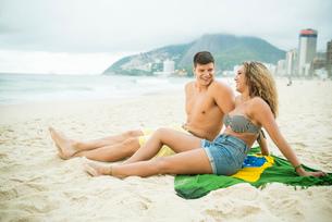 Young couple sitting on brazilian flag, Ipanema Beach, Rio de Janeiro, Brazilの写真素材 [FYI03515273]