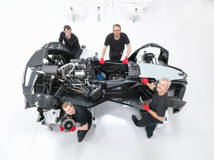 Portrait of engineers assembling supercar in sports car factory, overhead viewの写真素材 [FYI03515282]