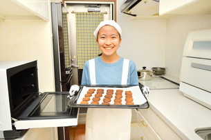 キッチンでクッキーを焼く女の子の写真素材 [FYI03515379]