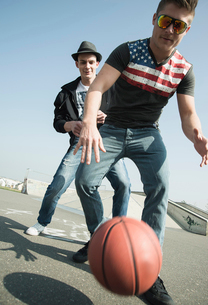 Young men playing basketball in skateparkの写真素材 [FYI03515622]