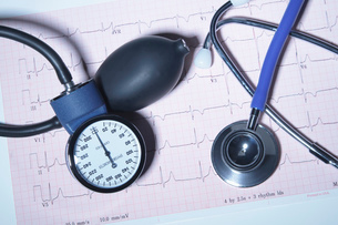Acoustic stethoscope and blood pressure gauge on an electrocardiogram printoutの写真素材 [FYI03515844]