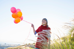 Young woman on grassy hill holding bunch of balloonsの写真素材 [FYI03515889]