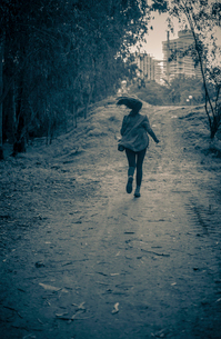 Young woman running from danger up dirt track toward apartment blocksの写真素材 [FYI03515943]