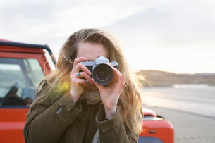Mid adult woman photographing with SLR in coastal parking lotの写真素材 [FYI03515979]
