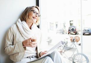 Senior woman having a coffee in cafe window seatの写真素材 [FYI03516017]