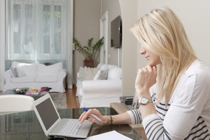 Young woman typing on laptop at home deskの写真素材 [FYI03516105]