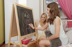 Girl drawing portrait of her mother on blackboardの写真素材 [FYI03516107]