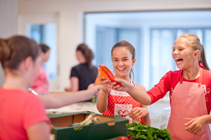 Teenage girls holding up chillies and carrot in kitchenの写真素材 [FYI03516119]
