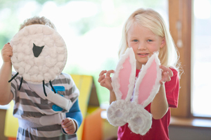 Boy and girl holding up sheep and rabbit creations at nursery schoolの写真素材 [FYI03516123]
