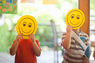 Two boys holding up smiley face masks at nursery schoolの写真素材 [FYI03516124]