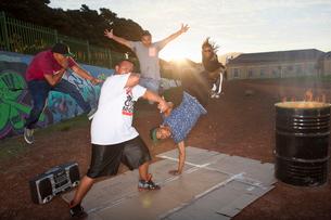 Group of five men breakdancing in park at duskの写真素材 [FYI03516148]