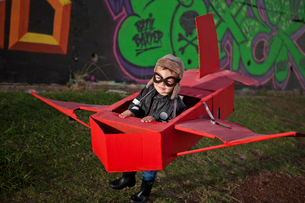 Boy wearing flying goggles running in toy airplane in park at nightの写真素材 [FYI03516150]