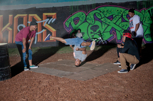 Group of men and boys breakdancing in park at nightの写真素材 [FYI03516174]