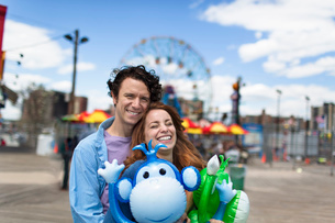 Portrait of couple and inflatable monkeys at amusement parkの写真素材 [FYI03516350]