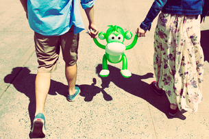Cropped rear view of couple holding hands with inflatable monkeyの写真素材 [FYI03516351]