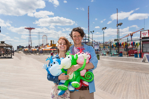 Portrait of couple with inflatable monkeys at amusement parkの写真素材 [FYI03516354]