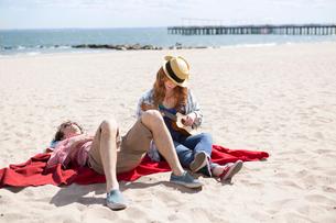 Couple sunbathing and playing ukulele on beachの写真素材 [FYI03516364]