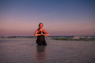 Mature woman practicing kneeling yoga pose on beach at sunsetの写真素材 [FYI03516443]