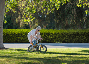 Three year old boy learning to cycle with grandmother in parkの写真素材 [FYI03516450]